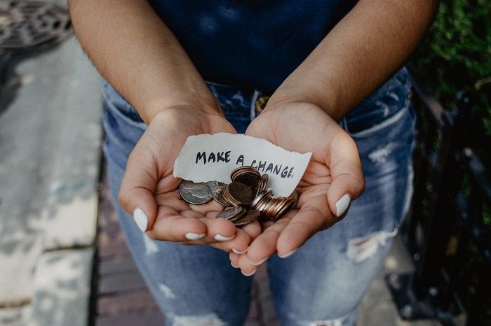 deux mains tiennent de la petite monnaie